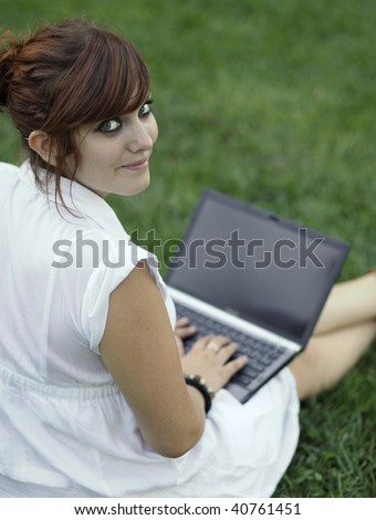 Pretty young woman working on a laptop computer outdoors, looking at the camera