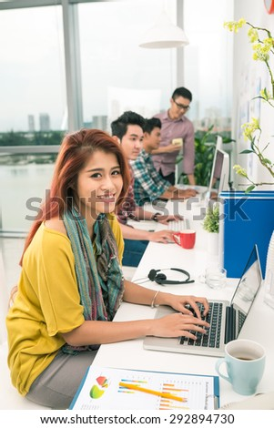 Pretty young woman working on laptop at her workplace
