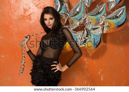 Pretty young women holding silver party balloons. Wearing sexy elegant dress  - stock photo