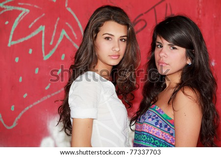 Pretty young women in a outdoor fashion scene with a red graffiti background.