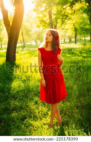 Pretty young women in red dress backlit  by sunset in front of green trees. - stock photo