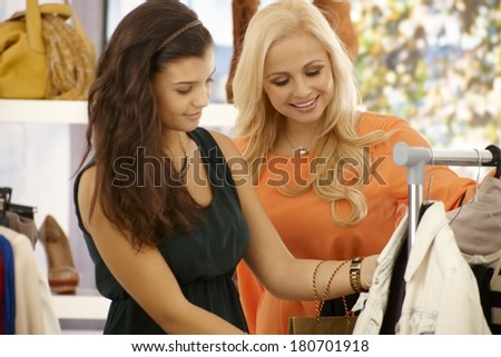 Pretty young women shopping together at clothes store, smiling. - stock photo