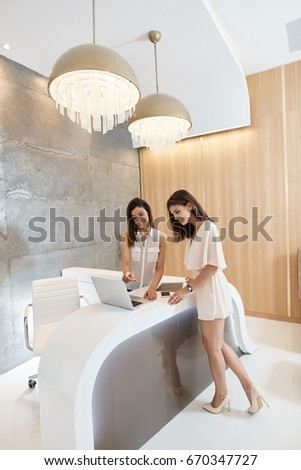 Pretty young women using laptop computer at reception of elegant salon.
