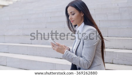 Pretty young worker sitting on steps with phone - stock photo