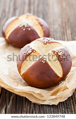 pretzel bun on wooden table - stock photo