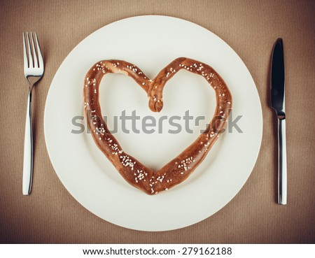 Pretzel in heart shaped on plate with cutlery, vignette toned