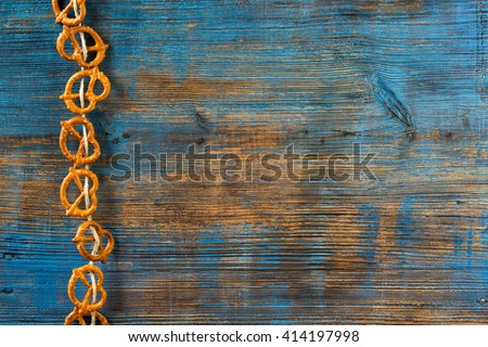 Pretzels hanging on a rope on rustic wooden background - stock photo