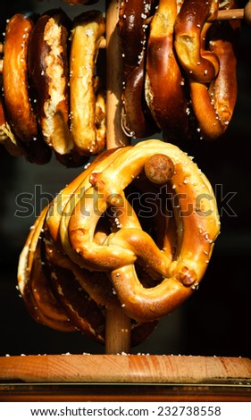 Pretzels hanging on wooden stand at Christmas food market in Paris. A game of light and shadow. - stock photo