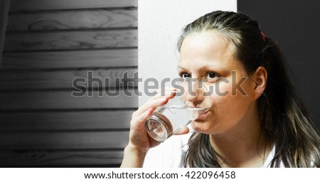 Prevention of dehydration and heat stress. Portrait of pretty young woman in white shirt drinking the glass of water on the grey background - stock photo