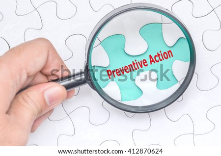 Preventive Action word with hand holding magnifying glass over jigsaw puzzle. Selective focus. - stock photo