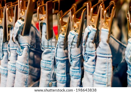 Preview jeans iron clothespins hanging in the closet  - stock photo