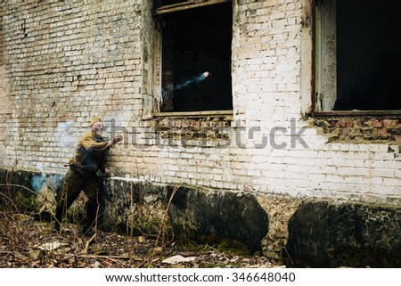 PRIBOR, BELARUS - April, 05, 2015: Unidentified re-enactor dressed as Soviet russian soldier throws a smoke bomb in a window of an abandoned building