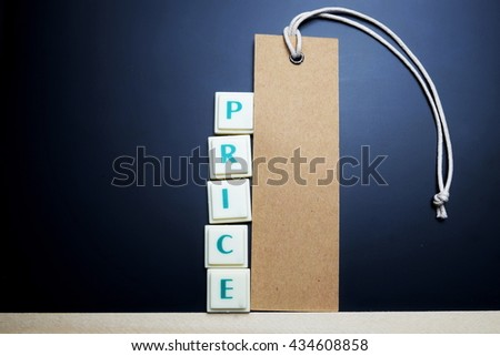 Price concept. The words spelled by letters with price tag, brown label on blackboard with wooden border. Space for texts. Dark tone. - stock photo