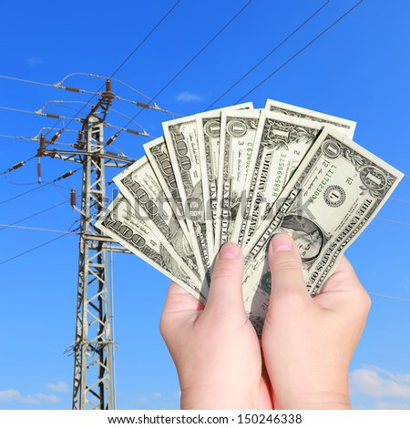 Price increase on electricity. Hands keep banknotes (Dollars) on an electricity pillar background. - stock photo