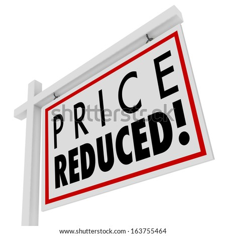 Price Reduced words on a home for sale sign to illustrate a home owner in distress and needing to sell immediately as a short sale or negotiated lower value to the right buyer - stock photo