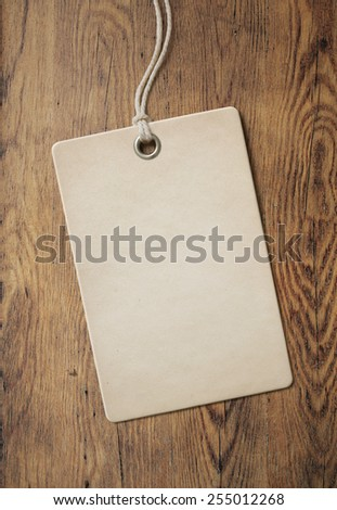 price tag or label on old wooden table background - stock photo
