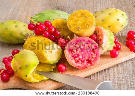 prickly pears and cranberries on cutting board - stock photo