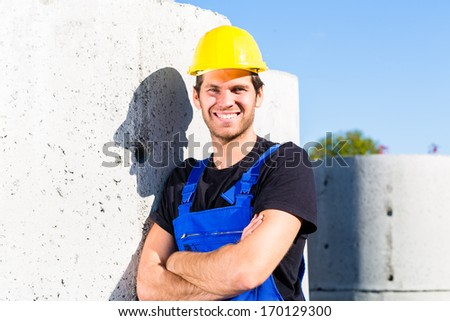 Pride builder standing on construction or building site with sewage or canalization concrete elements