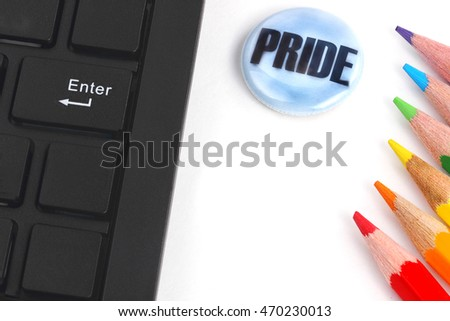 Pride concept surrounded by red, orange, yellow, green, blue and purple coloring pencils and enter tab on computer