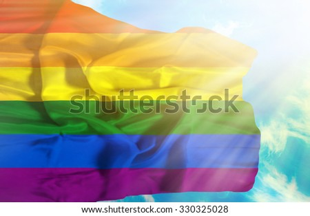 Pride waving flag against blue sky with sunrays - stock photo