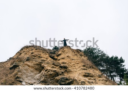 Priest bearded man raised his hands up on the hill above the town. Pastor posing outdoors in mountains - stock photo