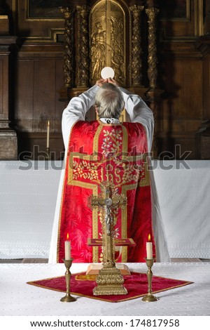 Priest during consecration the old way, with his back to the people, in a medieval church with 17th century interior - stock photo
