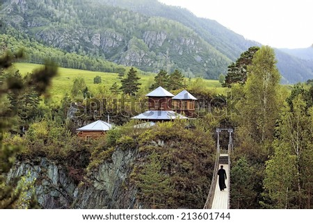 priest goes to Church on a hanging bridge. - stock photo