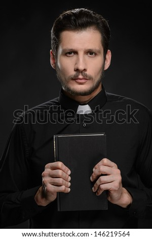 Priest holding Bible. Portrait of priest holding the Holy Bible - stock photo