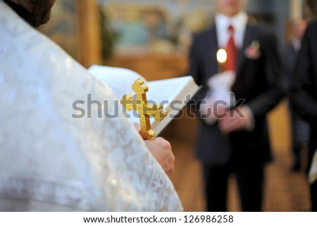 priest holding cross and bible at wedding ceremony - stock photo