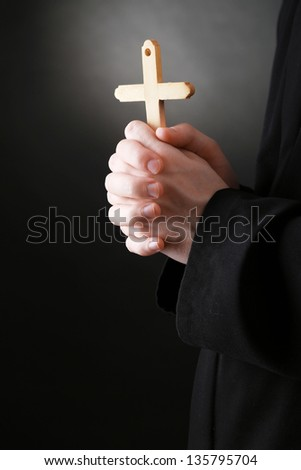 Priest holding cross, on black background - stock photo