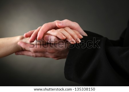 Priest holding woman hand, on black background - stock photo