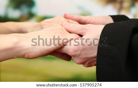 Priest holding woman hands, on green background - stock photo