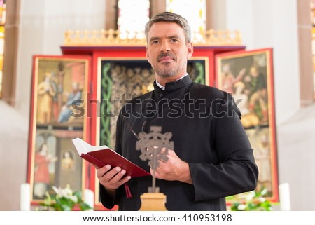 Priest in church with bible in front of altar - stock photo