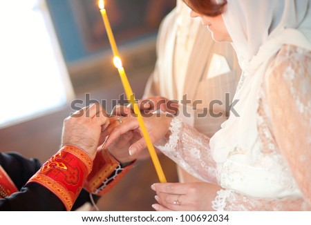 Priest is putting ring on bride's finger during orthodox wedding ceremony - stock photo