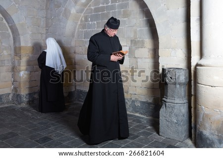 Priest passing a young nun along the walls of a medieval abbey - stock photo