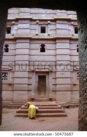 Priest praying outside the rock hewn church of Bet Amanuel at Laibela in Ethiopia - stock photo