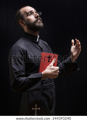 Priest praying with a bible - stock photo
