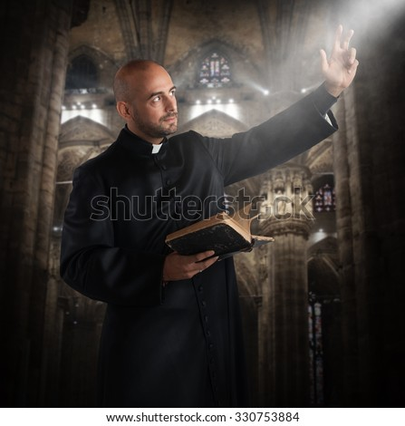 Priest prays in the church with bible - stock photo
