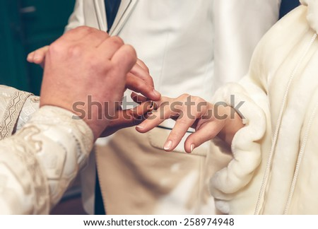 priest putting a ring on bride's finger during wedding ceremony - stock photo