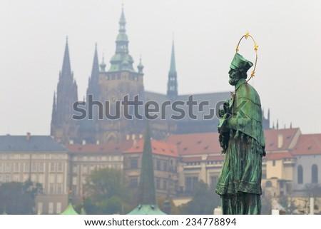 Priest statue on Charles bridge across Vltava river in cloudy autumn day, Prague, Czech Republic - stock photo