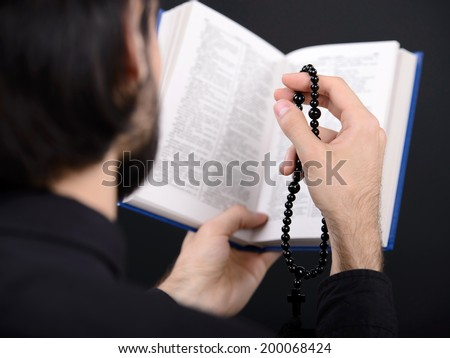 Priest with Holy Bible. Portrait of priest reading the Holy Bible - stock photo