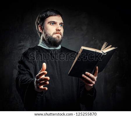 Priest with Prayer book against dark background - stock photo