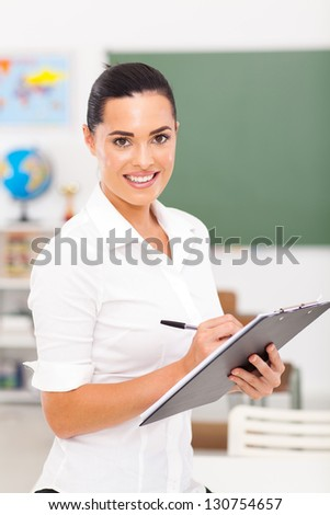 primary educator writing on clipboard