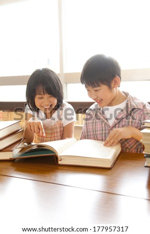 Primary Japanese boy and Japanese girl who read a book in the library