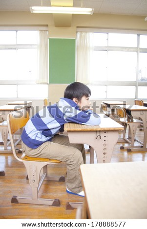 Primary Japanese boy lying on the desk boringly