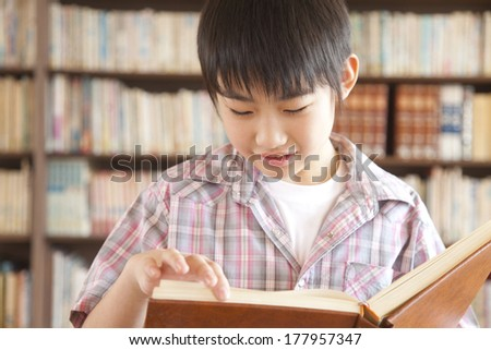 Primary Japanese boy reading a book in the library