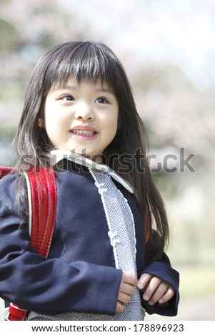 Primary Japanese girl standing under the cherry tree