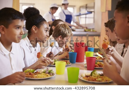 Primary school kids eat lunch in school cafeteria, close up - stock photo