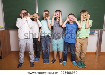 primary school kids looking through donuts in front of blackboard in a classroom - stock photo