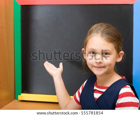 primary school pupil points hand on blackboard